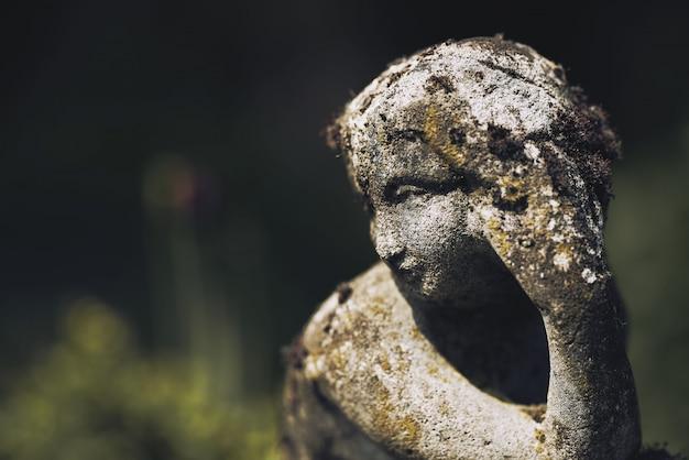 Gros plan d'une statue de pierre moussue rouille d'une femme