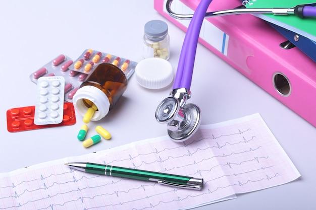 Gros plan stéthoscope couché sur prescription rx avec des pilules assorties. vie saine ou concept d'assurance.