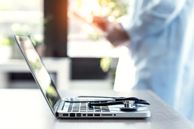 Gros plan d'un stéthoscope médical sur clavier d'ordinateur portable. arrière-plan flou d'un médecin examinant la documentation d'un patient en consultation.