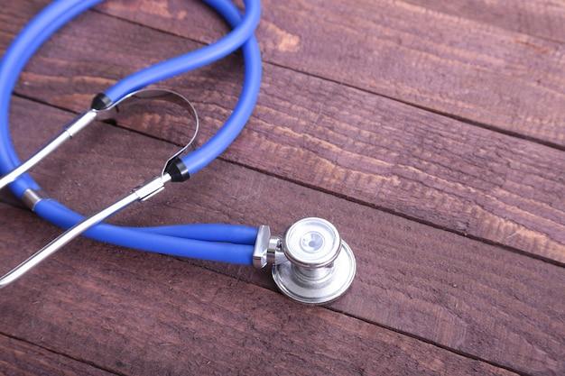 Gros plan d'un stéthoscope médical, isolé sur fond en bois.
