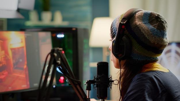 Gros plan sur un streamer jouant à un jeu vidéo de tir à la première personne à l'aide d'un ordinateur puissant rvb pendant un tournoi d'esport. joueur effectuant une compétition de jeux en ligne tard dans la nuit dans un home studio en streaming
