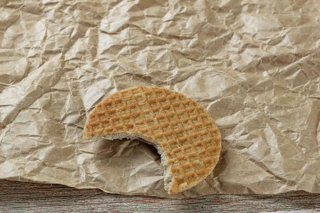 Gros plan de stroopwafel avec une morsure sur un papier brun.