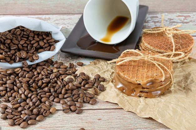 Gros plan sur des stroopwafels empilés sur du papier brun, à côté d'une tasse de café allongée.