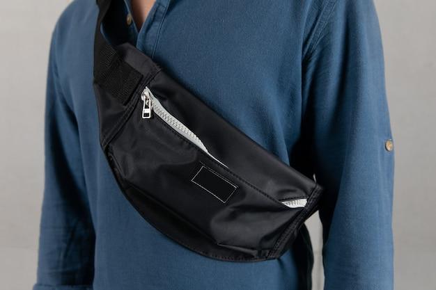 Gros plan en studio d'un modèle masculin en chemise à manches longues bleue suspendue à la mode urbaine petite bandoulière noire bandoulière sac banane décontracté sur fond gris devant.