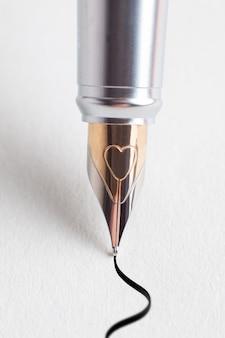Gros plan d'un stylo écrit sur du papier blanc.
