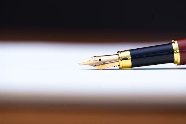 Gros plan d'un stylo plume ou stylo à encre avec du papier de cahier