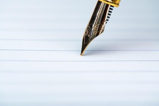Gros plan, de, stylo plume, ou, stylo encre, à, papier cahier, sur, table de travail en bois