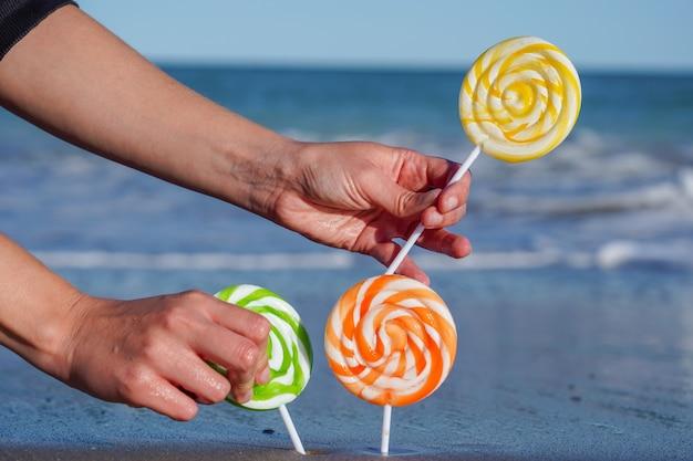 Gros plan de sucettes sucrées colorées sur la plage de sable