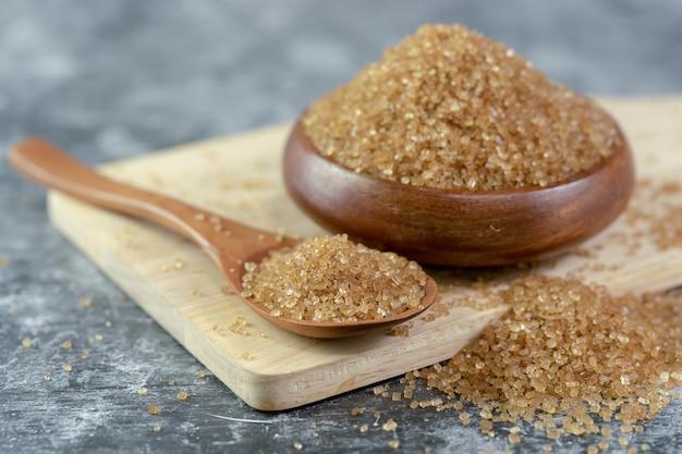 Gros plan de sucre sur une cuillère en bois.