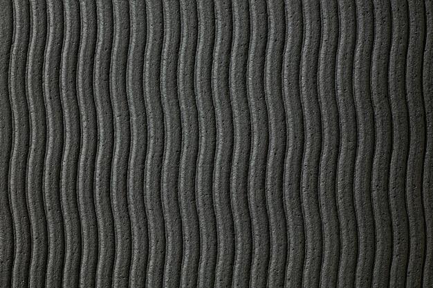 Gros plan de la surface du mur ondulé gris