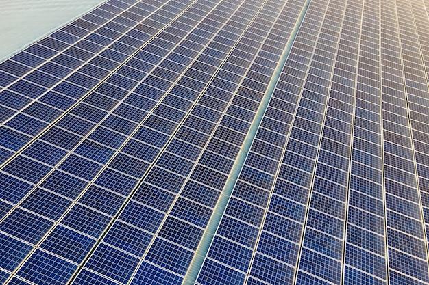Gros plan de la surface des panneaux solaires photovoltaïques bleus montés sur le toit du bâtiment pour produire de l'électricité écologique propre. production de concept d'énergie renouvelable.