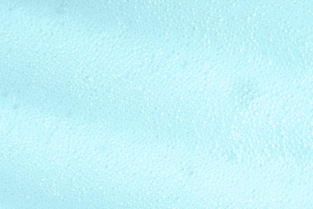 Gros plan de surface savonneuse bleue. texture de produit de soin nettoyant moussant à partir de savon