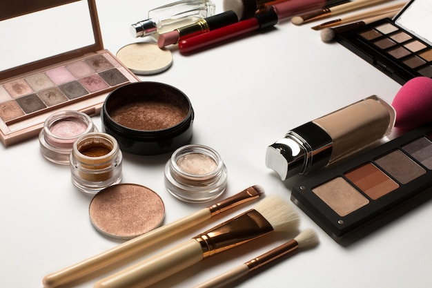 Gros plan sur des surligneurs, des ombres à paupières crème et des palettes de maquillage minéral sur fond blanc. espace pour le texte