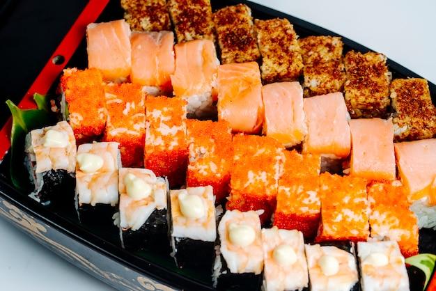 Gros plan de sushi serti de saumon, crevettes, tobiko rouge et rouleaux chauds