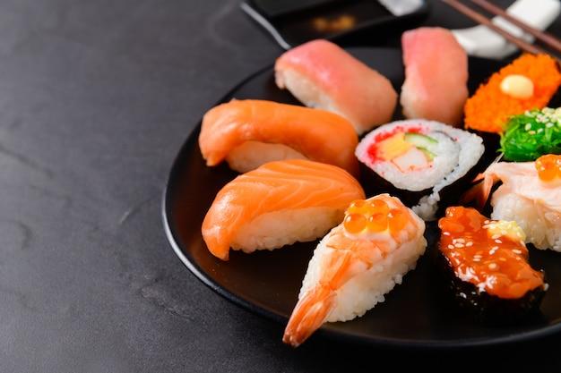 Gros plan de sushis sashimi sur un plat noir,
