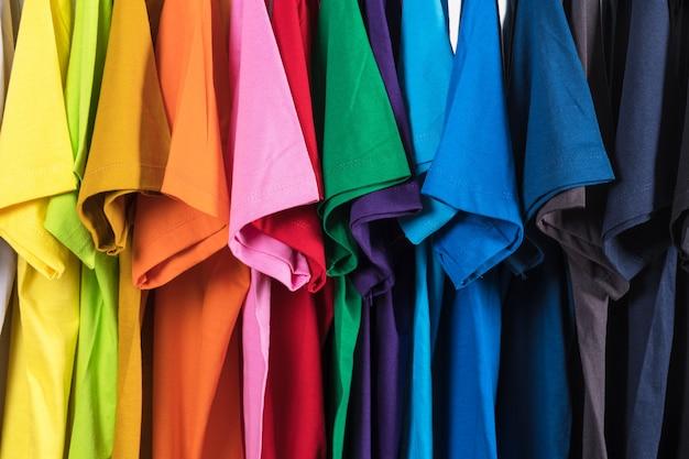 Gros plan des t-shirts, des vêtements sur des cintres sur fond blanc