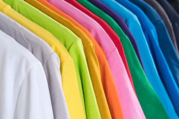 Gros plan de t-shirts, vêtements sur cintres sur fond blanc