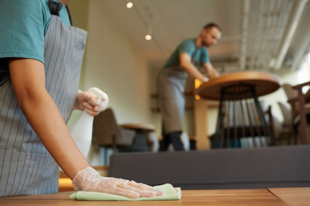Gros plan sur une table de nettoyage de serveuse méconnaissable dans un café avec des accents en bois chaleureux, espace pour copie