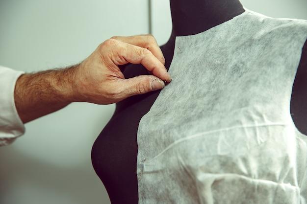 Gros plan de la table des tailleurs avec des mains masculines traçant le modèle de fabrication de tissu pour les vêtements en studio atelier traditionnel. l'homme au métier féminin. concept d'égalité des sexes
