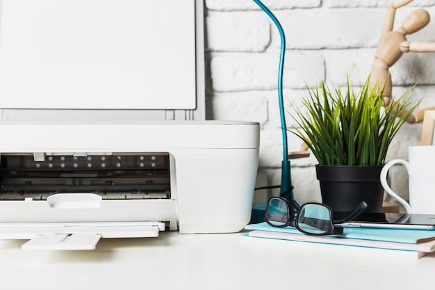 Gros plan d'une table de travail à la maison avec imprimante et fournitures