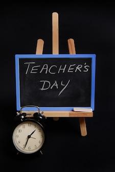 Gros plan sur un tableau noir à la craie avec inscription journée de l'enseignant, debout sur un chevalet de table en bois, à côté d'un réveil noir, isolé sur fond noir avec espace de copie.