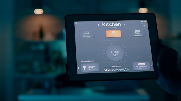 Gros plan sur une tablette avec une application de maison intelligente active détenue par un homme