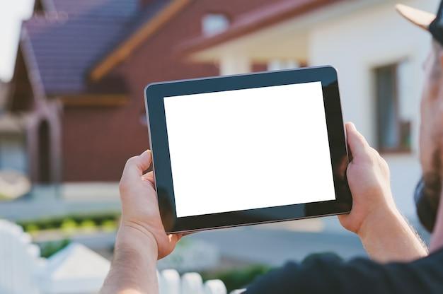 Gros plan d'une tablette dans les mains d'un homme, sur le fond de la maison.