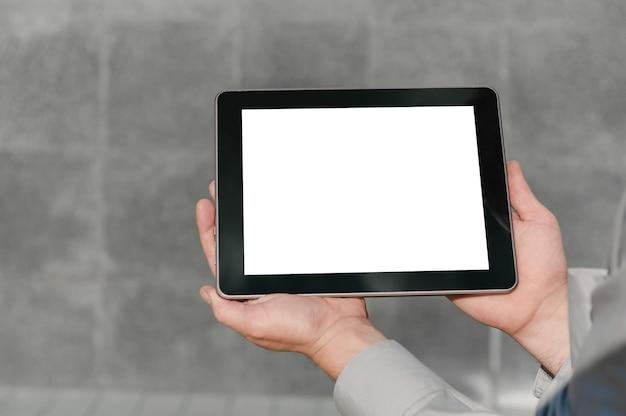 Gros plan, tablette maquette, présentation du plan d'affaires, mains de l'homme. sur fond de mur de béton.