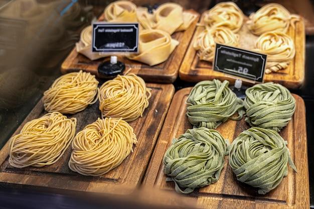 Gros plan de tagliatelles de pâtes vertes fraîches maison crues. pâtes crues traditionnelles italiennes fraîches sur le comptoir dans le magasin avec des étiquettes de prix flou