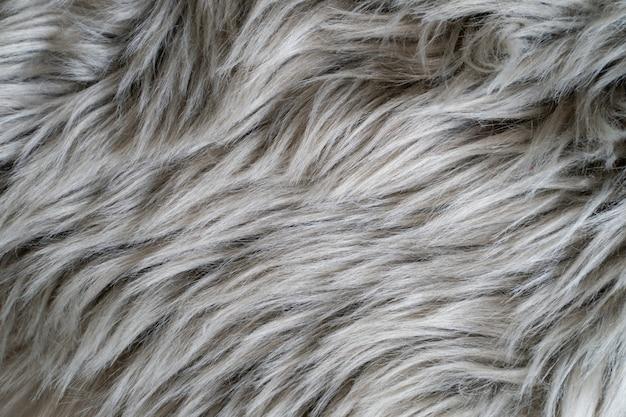 Gros plan d'un tapis en peau de mouton gris, fourrure de tapis.