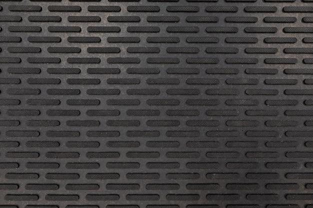 Gros plan de tapis de sol en caoutchouc noir.