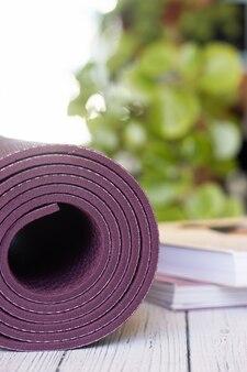 Gros plan d'un tapis de yoga violet avec des livres sur un plancher en bois blanc.