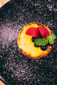 Gros plan la tarte au fromage avec des tranches de fraises et de mûres avec du sucre glace.