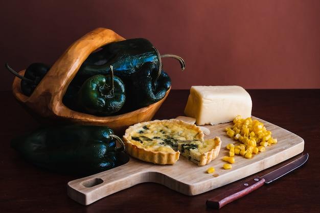 Gros plan de tarte, de fromage et de maïs sur la planche à découper et de poivrons verts dans la plaque de bois