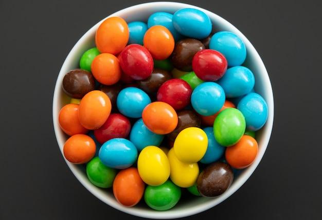 Gros plan d'un tas de bonbons enrobés de chocolat coloré, fond de chocolat