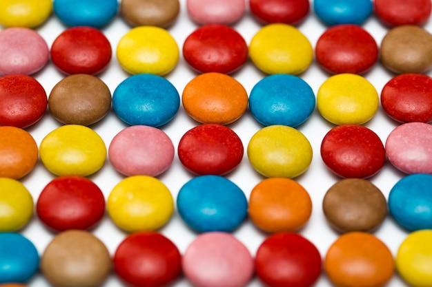 Gros plan d'un tas de bonbons enrobés de chocolat coloré, motif chocolat, fond de chocolat