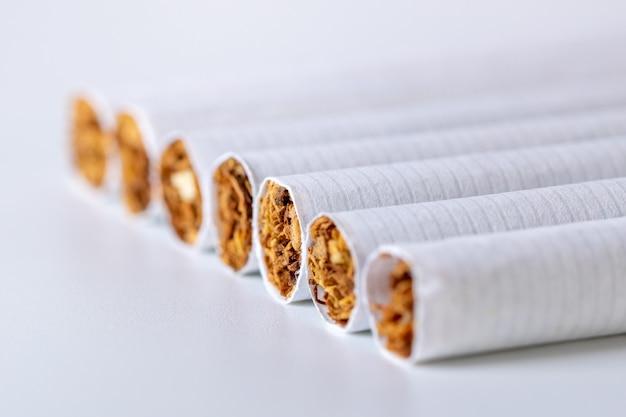 Gros plan d'un tas de cigarettes sur fond blanc