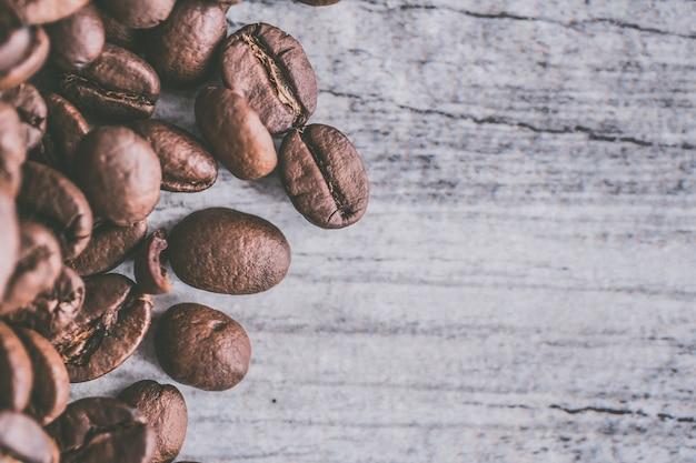 Gros plan d'un tas de graines de café sur un fond en bois gris