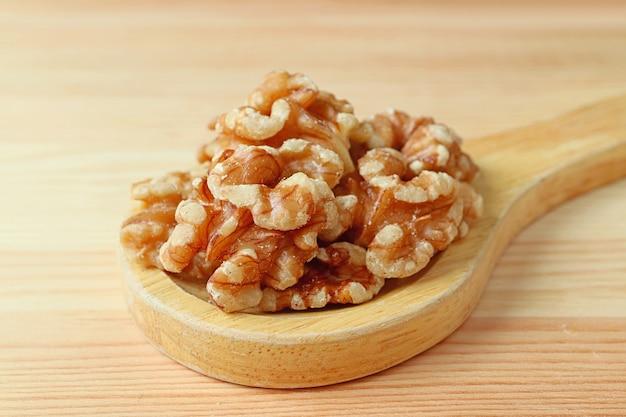 Gros plan tas de noyaux de noix sur une cuillère en bois sur table en bois