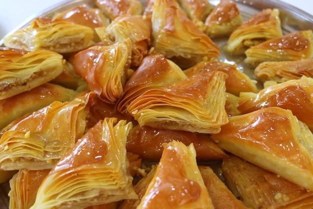 Gros plan tas de pâtisseries baklava sur un grand plateau avec mise au point sélective