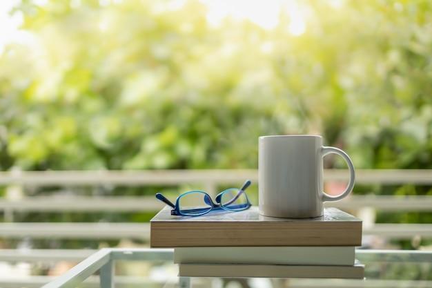 Gros plan d'une tasse blanche de café chaud sur une pile de livres avec des lunettes de lecture bleues avec la nature verte en arrière-plan.