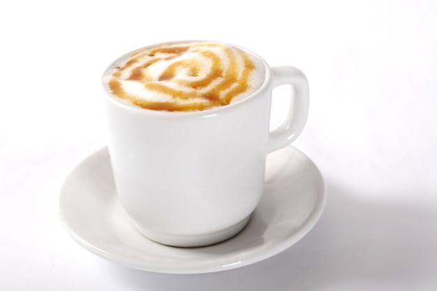Gros plan d'une tasse blanche de cappuccino avec de la mousse de lait à la vapeur à motifs sur le dessus