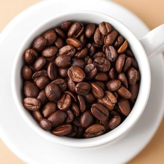 Gros plan d'une tasse blanche avec des grains de café arabica. photo carrée.