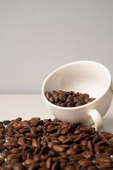 Gros plan tasse blanche remplie de grains de café