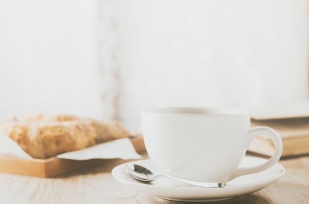 Gros plan d'une tasse à café blanche avec un croissant sur une table en bois avec ton vintage