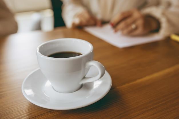 Gros plan sur une tasse de café devant des mains féminines écrivant des notes lors d'une réunion créative, d'une discussion, d'un projet de travail au bureau. concept de finance, d'affaires, de pouvoir des filles, d'inclusion, de diversité, de féminisme.