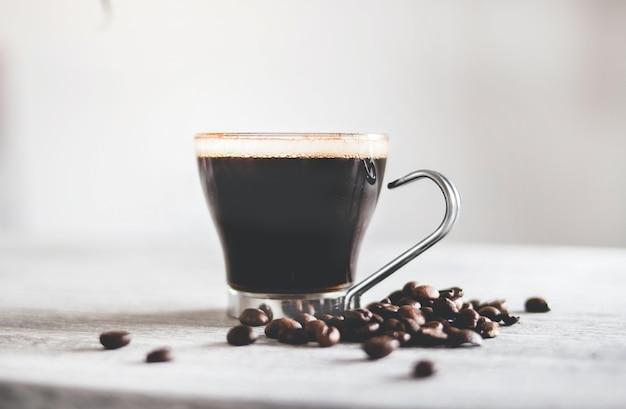 Gros plan d'une tasse de café noir sur la table avec des grains torréfiés sous les lumières