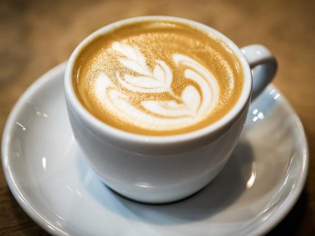 Gros plan d'une tasse de cappuccino avec de l'art du café magnifique