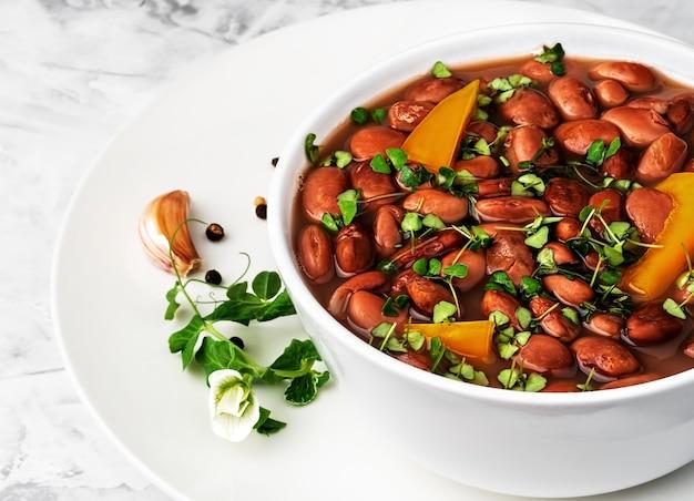 Gros plan d'une tasse de haricots rouges bouillis décorés de feuilles de basilic