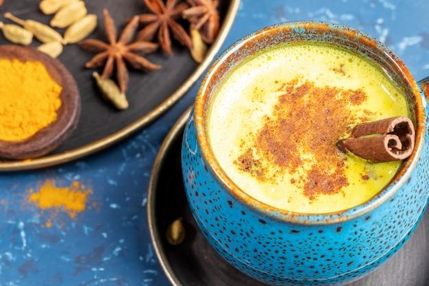 Gros plan tasse de lait au curcuma doré ayurvédique indien traditionnel avec cardamome, anis et cannelle sur bleu.